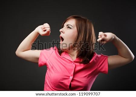 Studio portrait of a sleepy businesswoman yawning - stock photo