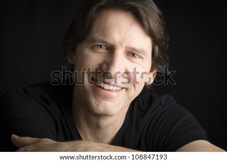 Studio Portrait of a smiling man with arms folded - stock photo