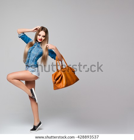 Studio portrait of a stylish square women denim dress with long blond hair, red lips, long legs,leather bag in hand. Clothing jeans, bag leather, slender figure. Style,fashion,beauty. - stock photo