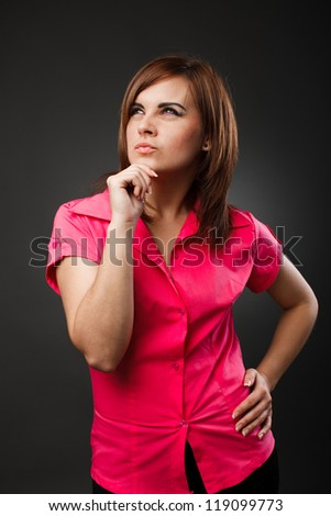 Studio portrait of a thoughtful young businesswoman over gray background - stock photo