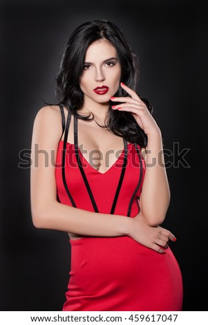 Studio portrait of a woman.Beautiful woman in a red dress on a black background.ATTRACTIVE stylish woman in fashion clothes.Brunette woman with red lips.charming woman looking at the camera - stock photo