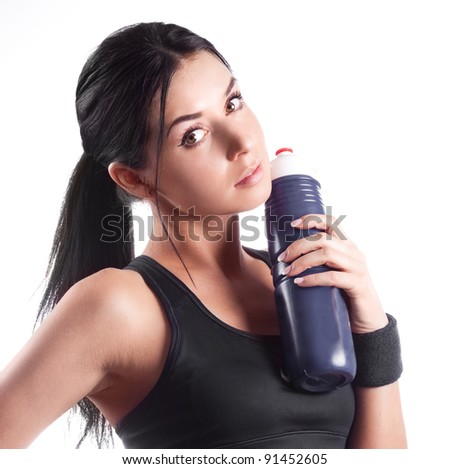 studio portrait of a young beautiful sporty woman, holding a bottle with water - stock photo