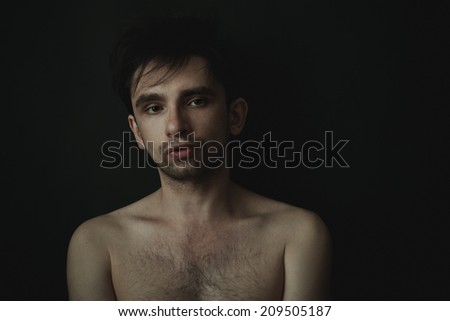 Studio portrait of a young handsome man on a black background - stock photo