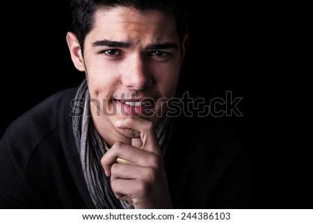 Studio portrait of a young man smiling with an inquisitive expression on black background. - stock photo