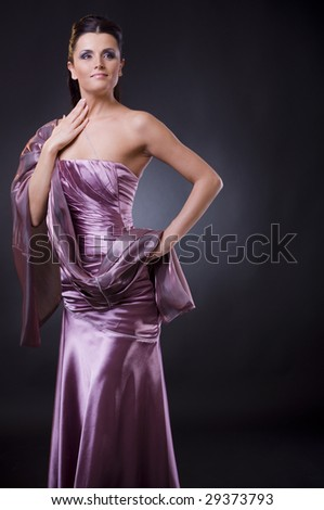 Studio portrait of a young woman wearing a light purple evening dress with stole. - stock photo