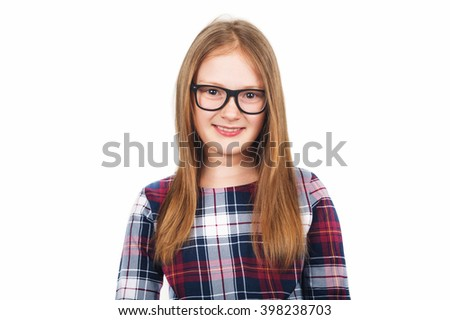 Studio portrait of adorable little girl of 8-9 years old, wearing eyeglasses, standing against white background - stock photo