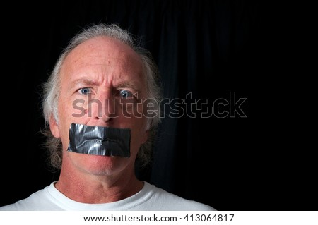 Studio portrait of an older blue eyed man with mouth duct taped closed, looking distraught, black background with copy space. Political correctness or freedom of speech concept. - stock photo