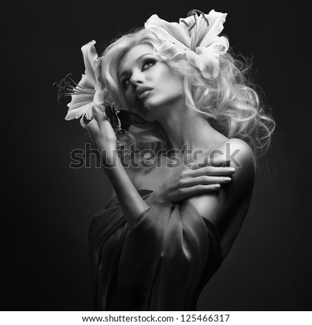 studio portrait of beautiful blonde with wide opened eyes wearing flowers in her hair and tropical butterfly sitting on her hand on dark background - stock photo