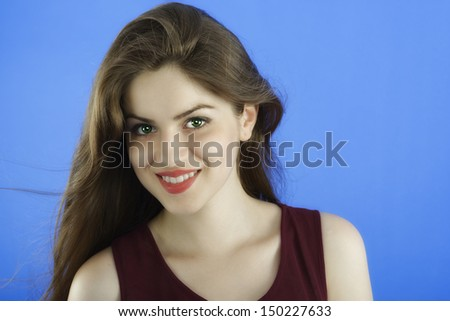 studio portrait of beautiful woman with long hair on blue background - stock photo