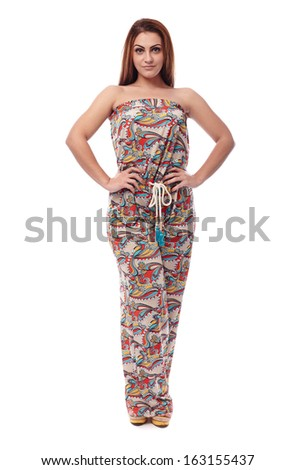 Studio portrait of beautiful young woman wearing elegant overall and standing akimbo isolated on white background - stock photo