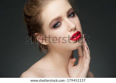 Studio portrait of beautiful young woman with stylish makeup with red lipstick  - stock photo