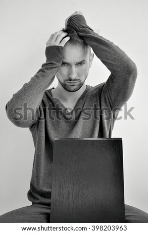 Studio portrait of caucasian bearded young man. Front view, with bold aggresive facial expression. Sitting on chair, touching his face with  hands. Posing. Test shot - stock photo