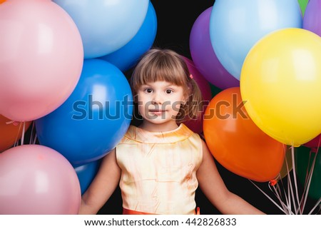 Studio portrait of Caucasian blond little girl with colorful balloons over black - stock photo