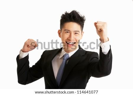 Studio Portrait Of Chinese Businessman Celebrating - stock photo