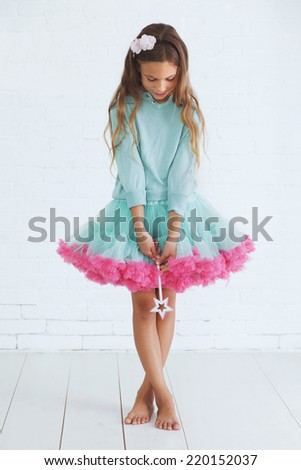 Studio portrait of cute little princess girl wearing holiday candy tutu skirt holding magic wand - stock photo
