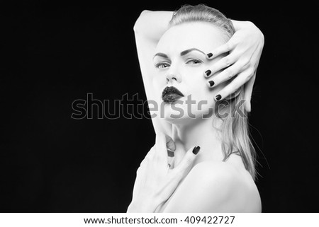 Studio portrait of female caucasian young blonde model with black lipstick and nails. Isolated on black background. Studio portrait. Black and white. - stock photo