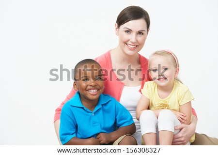 Studio Portrait Of Female Pre School Teacher With Pupils - stock photo