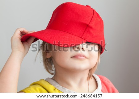 Studio portrait of funny baby girl in red baseball cap over gray wall background - stock photo