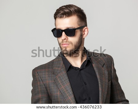 Studio portrait of handsome elegant young man in brown jacket posing against gray background. - stock photo