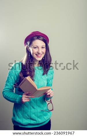 Studio portrait of holding a book & big glasses hipster or hippie pretty girl having fun wearing knitting sweater happy smiling and looking at camera over copy space background  - stock photo