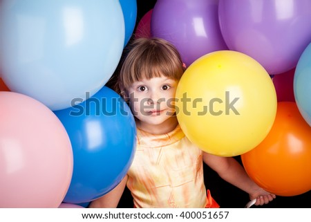Studio portrait of little Caucasian blond girl with colorful balloons - stock photo