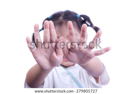 Studio portrait of little girl showing stop hand sign or signal in front of face - stock photo