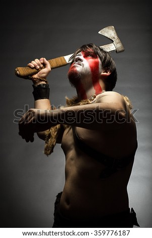studio portrait of man in war paint, with an ax in his hand, a warrior brandishing an ax up furiously, indian. - stock photo