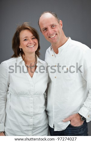 Studio portrait of middle aged couple wearing white shirt isolated on grey background - stock photo