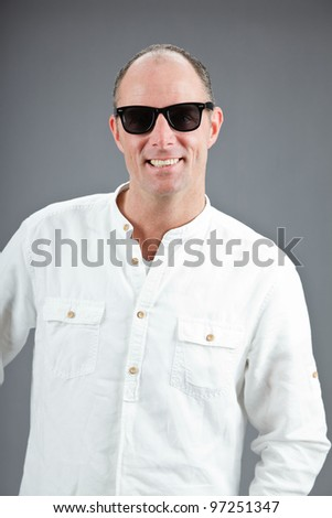 Studio portrait of middle aged woman with sunglasses and white shirt isolated on grey background - stock photo