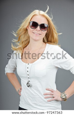 Studio portrait of pretty young woman wearing sunglasses and white shirt isolated on grey background - stock photo