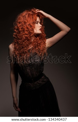 studio portrait of redhead woman with long hair on dark background - stock photo