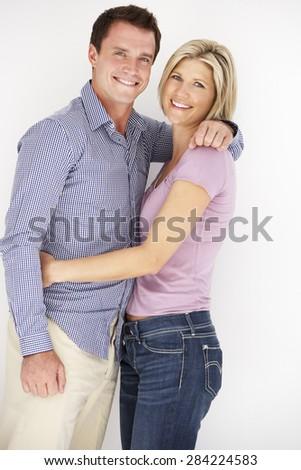 Studio Portrait Of Romantic Couple Embracing Against White Background - stock photo