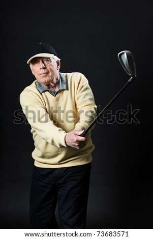 Studio portrait of senior golf man with yellow shirt and black cap making swing with golf club. Black background. - stock photo