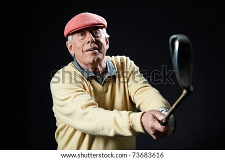 Studio portrait of senior golf man with yellow shirt and red cap making swing with golf club. Black background. - stock photo