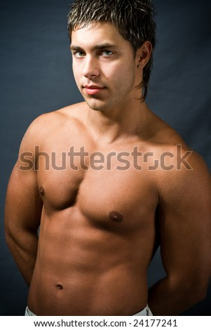 Studio portrait of shirtless muscular young man - stock photo