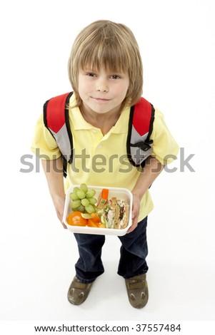 Studio Portrait of Smiling Boy Holding Lunchbox - stock photo