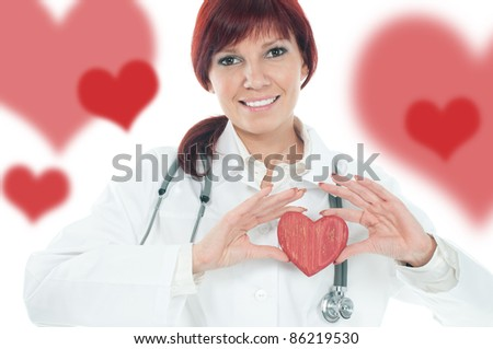 Studio portrait of successful cute young female cardiologist holding a wooden heart - stock photo