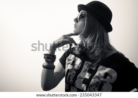 Studio portrait of teenage hipster girl wearing trendy hat and sunglasses over olive copy space background - stock photo