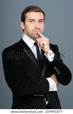 Studio portrait of thinking young business man. Black suit and tie. - stock photo