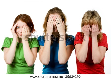 Studio portrait of three female friends covering their eyes with their hands, the first woman peeking out from behind one hand.  Isolated on a white background. - stock photo