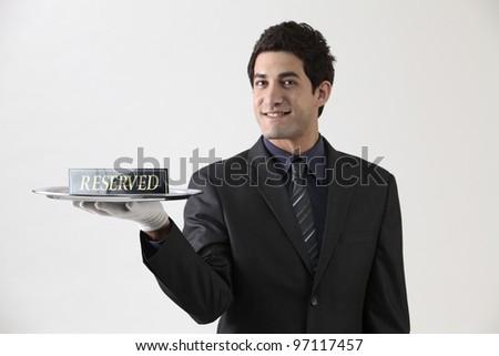 Studio portrait of waiter holding reserved sign - stock photo
