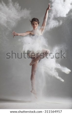 Studio portrait of woman dancing with flour - stock photo