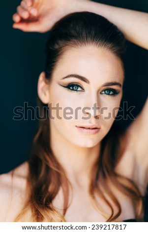 Studio Portrait of Young Attractive Woman close up with beautiful blue eyes looking at camera arm over head mouth slightly open - stock photo