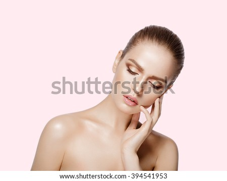 Studio portrait of young beautiful model with hands near her face on pink background. Perfect fresh clean skin. professional makeup. Brunette hair. Hands touching her face. Not isolated - stock photo