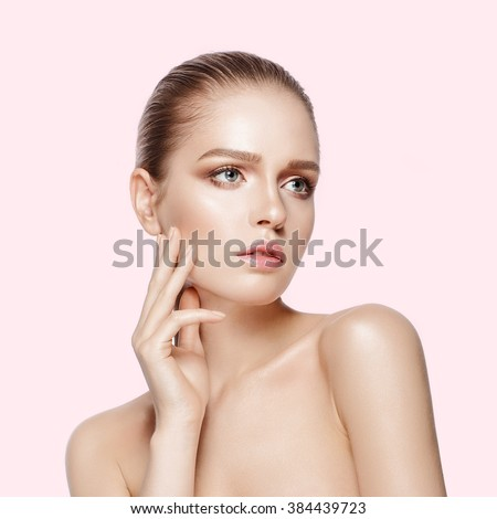 Studio portrait of young beautiful model with professional makeup on pink background. Perfect fresh clean skin. Deep blue eyes. Brunette hair. One hand touching head. Not isolated - stock photo