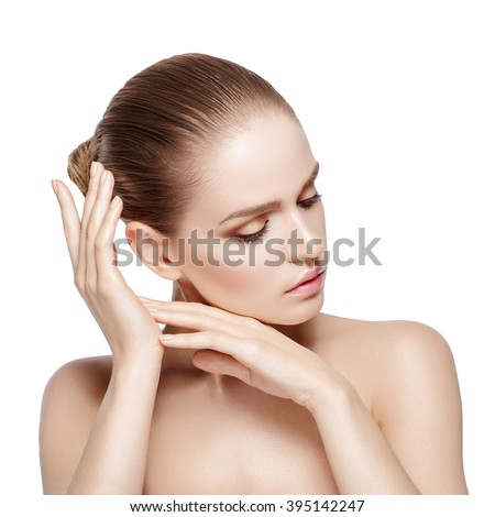 Studio portrait of young beautiful model with professional makeup on white background. Perfect fresh clean skin. Brunette hair. Hands near her head. Closed eyes. Isolated - stock photo