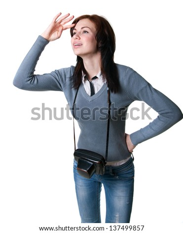 Studio portrait of young beautiful woman model holding her camera in a special leather case, looking with anticipation for some places ahead of her to take photos. Isolated on white, copy space - stock photo