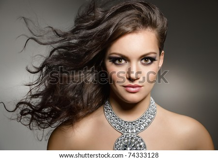 studio portrait of young gorgeous brunette with evening make up - stock photo