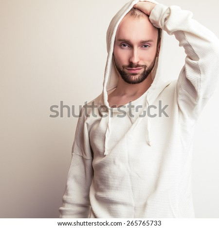Studio portrait of young handsome man in white sweater with hood. - stock photo