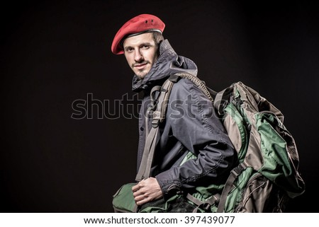 Studio portrait of  young handsome man wearing red beret , winter jacket and backpack  . vintage fashion winter male clothing  - stock photo